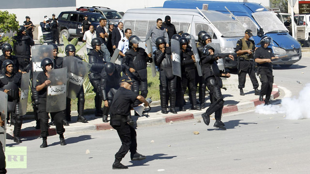 Protesters run for cover from riot police during a demonstration in front of the U.S. Embassy in Tunis
