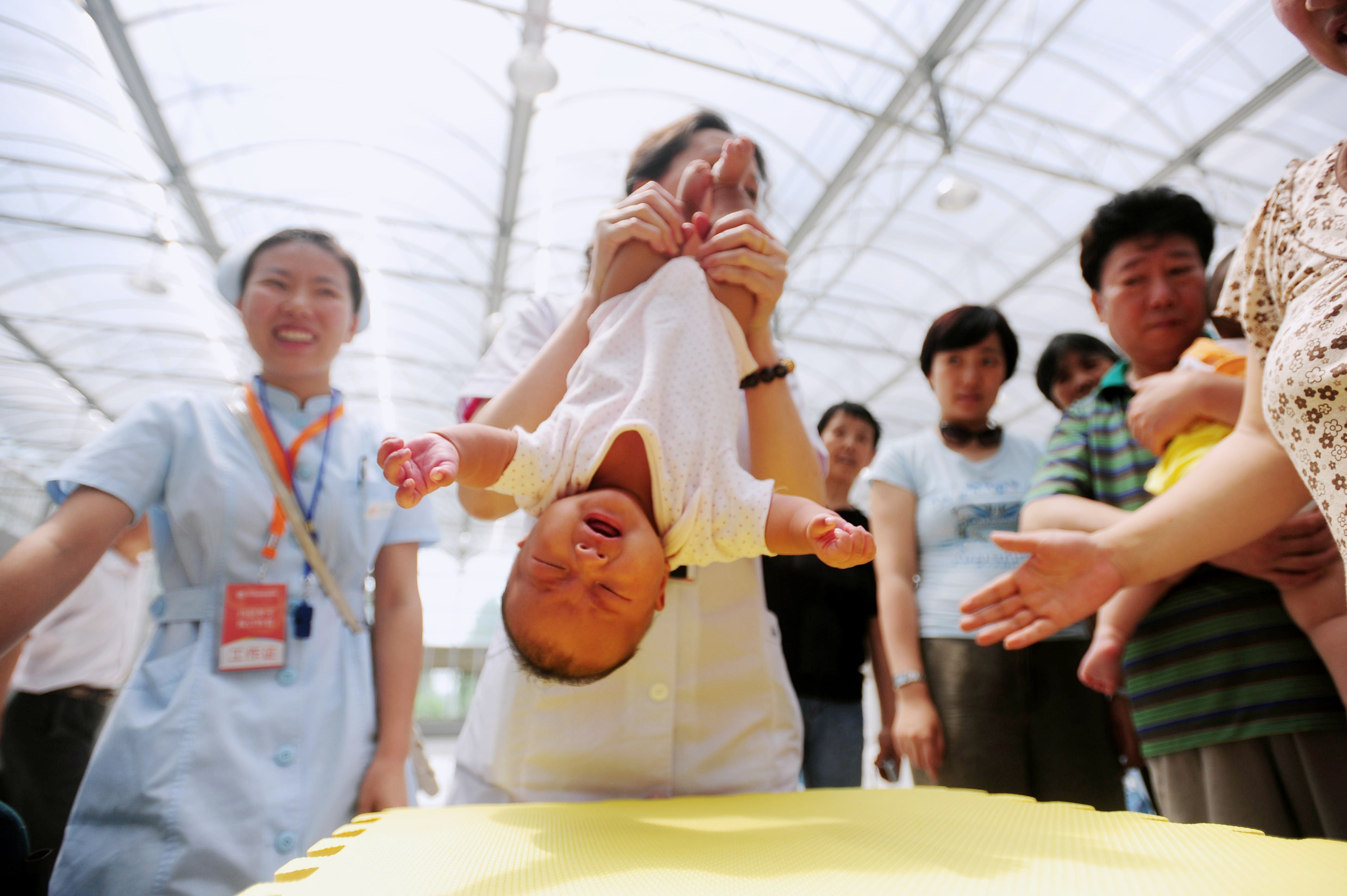 A doctor shows a group of Chinese parents how to help their babies exercise as they take part in an activity to celebrate the upcoming International Children's Day, in Beijing on May 31, 2010. The Chinese tradition of grandparents helping young couples with their kids still exists but is fraught with difficulties, from conflicts over how to raise the children to the fading strength of the elder generation. CHINA OUT AFP PHOTO