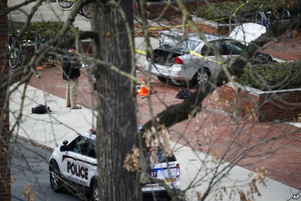 A car sits inside a police line as authorities respond to an attack at Ohio State University, Nov. 28, 2016, in Columbus, Ohio. A man plowed his car into a group of pedestrians and began stabbing people before he was shot to death by a police officer.