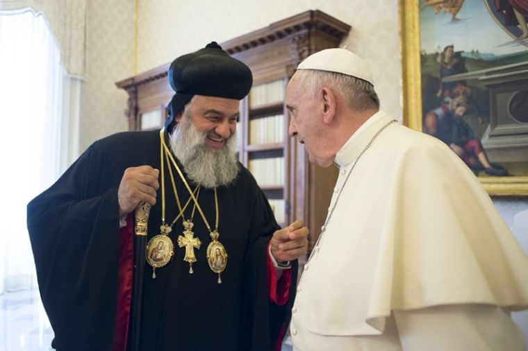 Pope Francis (R) talks with Ignatius Aphrem II, Syriac Orthodox Patriarch of Antioch, during a meeting at the Vatican.